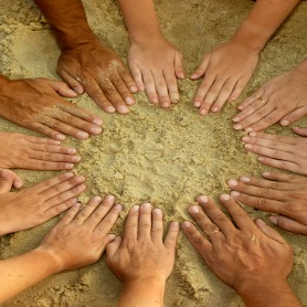 Many hands in a circle on beach